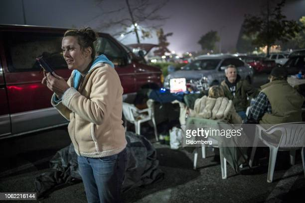 A Camp Fire evacuee talks on a mobile phone while camping in a Walmart Inc store parking lot in Chico California US on Thursday Nov 15 2018 The...