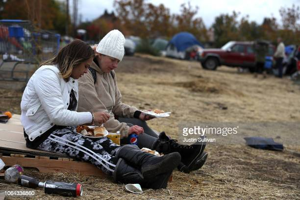 Camp Fire evacuees Magen Farris and Amy Sheppard have a Thanksgiving meal in a makeshift evacuation camp next to a Walmart store on November 22 2018...