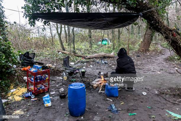 A camp of immigrants hidden in the woods in Calais France on December 20 2017 Immigrant from Bangladesh is cooking and getting worm by the fire
