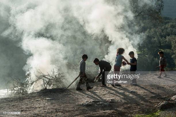 Camp residents walk past burning plastic refuse in the Moria camp on March 12, 2020 in Mytilene, Greece. The Moria Refugee Camp near Mytilene on the...