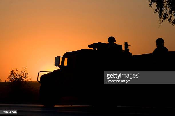 Camp Speicher, Iraq - A US Army Humvee with soldiers in the back at sunset.