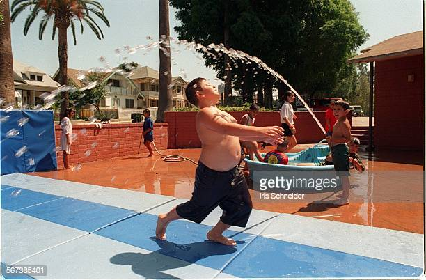 LSCamp#1IS8/1Kids from Hollenbeck Park day camp in East LA get wet under hose on the cement patio of the community center where their camp is held...