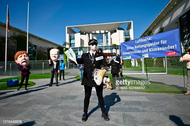Campact activists wearing masks of German Chancellor Angela Merkel and German Finance Minister and ViceChancellor Olaf Scholz dressed as a Lufthansa...