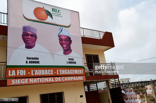 Campaign billboard and posters with photographs of the Benin opposition candidate for the Dynamics Restoring Confidence party, Corentin Kohoue and...