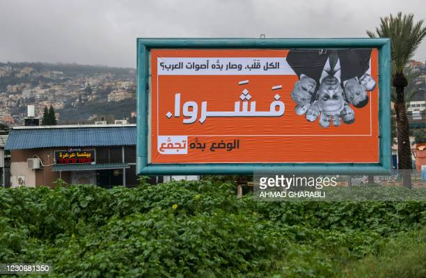 """Campaign billboard for the Balad Party, part of the joint Arab list, reads in Arabic """"Now they all turned around, wanting Arab votes? They wish!"""", in..."""