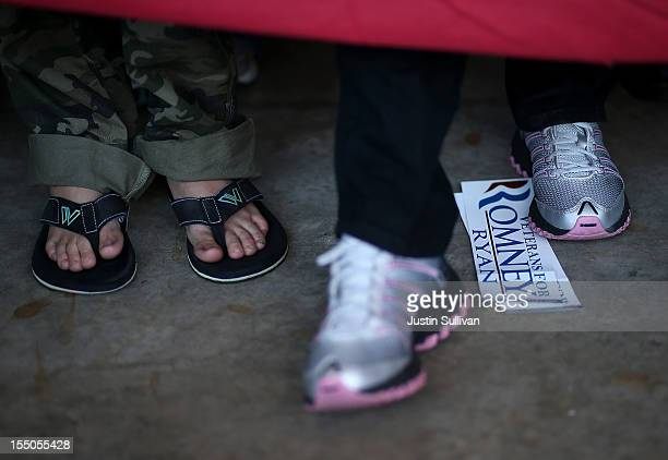 A campaign bumper sticker for Republican presidential candidate former Massachusetts Gov Mitt Romney sits next to the feet of supporters during...