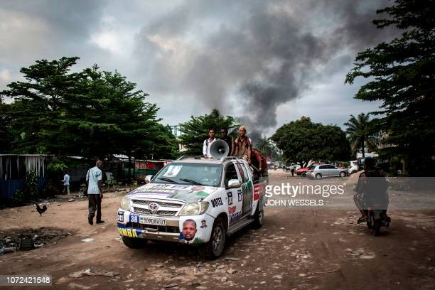 A campaign car is seen as smoke rises from a fire at the independent national electoral commission's warehouse on December 13 2018 in Kinshasa ten...