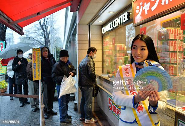 Campaign girl Miku Ishitani displays sample lottery tickets as people queue up to purchase tickets for the 'Green Jumbo Lottery' as the first tickets...