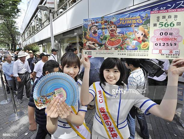 Campaign girls Akari Kamimura and Yuka Kurihara display lottery tickets and a giant mock ticket for the 300 million yen 'Summer Jumbo Lottery' at a...
