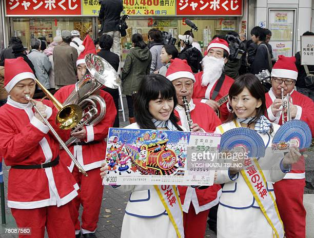 Campaign girls Arata Matsumoto and Risa Sugimoto display smple lottery tickets for the 300 million yen YearEnd Jumbo Lottery in front of a Tokyo...