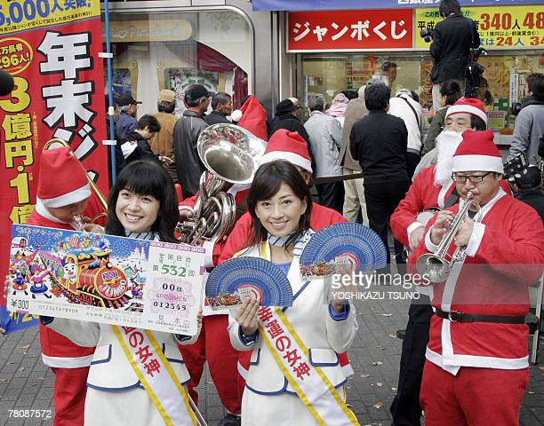Campaign girls Arata Matsumoto and Risa Sugimoto display smple lottery tickets for the 300 million yen YearEnd Jumbo Lottery before a Tokyo ticket...