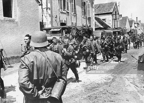 Campaign in the west / battle of France 10.05.-: German infantry marching through a village/ small town in france.Juni 1940 No further information.-...