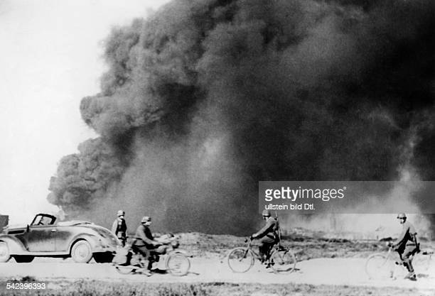 2WW Campaign in the west / battle of France 1940 german bicycle patrol at Dunkirk behind burning oil tanksEarly June 1940