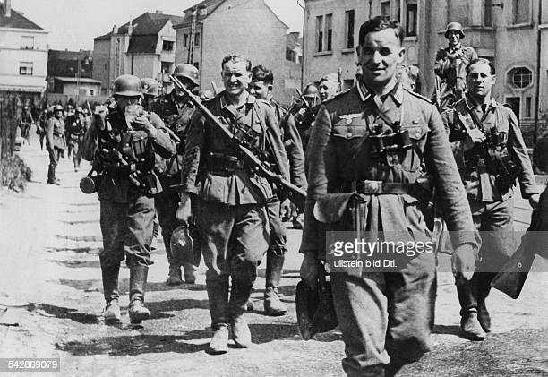 Campaign in the west / battle of france: german infantry entering Belgium: marching column passing a village - ca. 10./ - photo: Heinrich Hoffmann