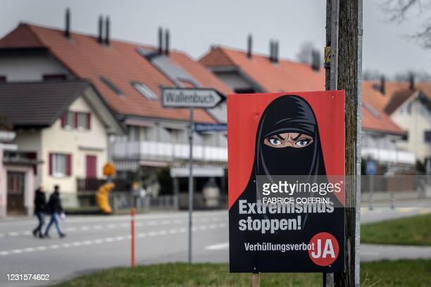 """Campaign poster, in favour of the """"burqa ban"""" initiative reading in German: """"Stop extremism!"""" is seen in Biberen near Bern on March 7, 2021 as..."""