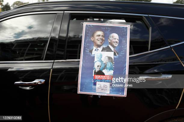 A campaign poster of former President Barack Obama Vice President Joe Biden and Sen Kamala Harris is seen on a car while Obama campaigns for...
