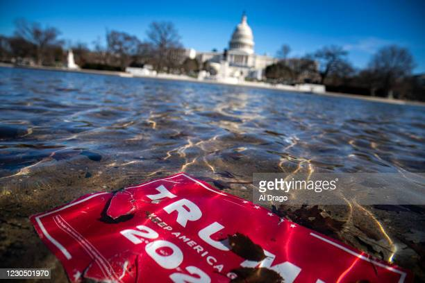 Campaign sign for U.S. President Donald Trump lies beneath water in the Capitol Reflecting Pool, on Capitol Hill on January 9, 2021 in Washington,...