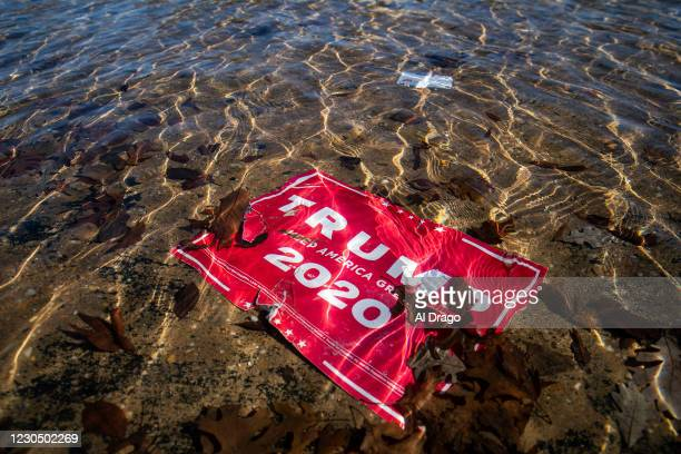 Campaign sign for U.S. President Donald Trump lies beneath water in the Capitol Reflecting Pool, near the West Front of the U.S. Capitol on January...