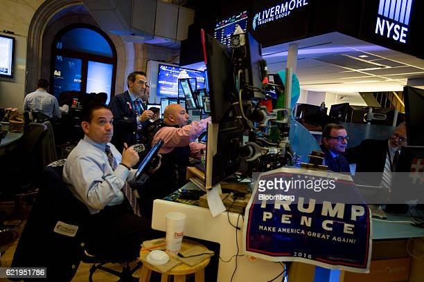 A campaign sign for US Presidentelect Donald Trump and US Vice Presidentelect Mike Pence hangs on a desk while traders work before the opening bell...