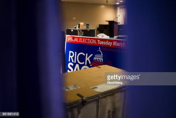 A campaign sign standing at a stage is seen through an opening between curtains ahead of an election night rally with Rick Saccone Republican...