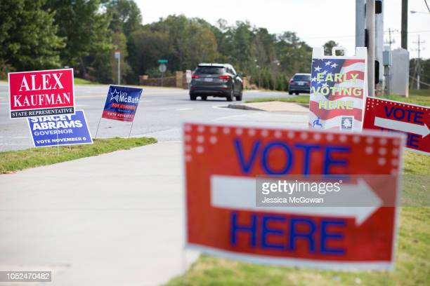 Campaign signs and early voting signs line a road in Roswell Georgia on October 18 2018 Early voting started in Georgia on October 15th Georgia's...