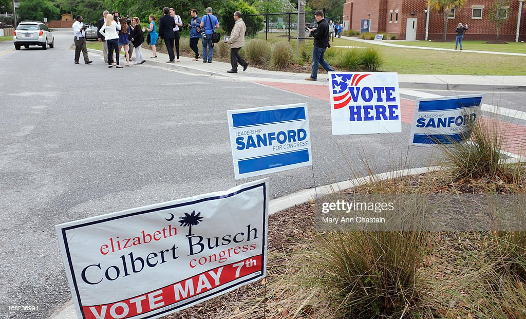 Campaign signs are stuck in a lawn as Elizabeth Colbert Busch speaks to media after casting her vote in a special election runoff with former South Carolina Gov. Mark Sanford for a seat in the 1st Congressional District May 7, 2013 in Charleston, South Carolina. Voters are deciding between Sanford, a Republican seeking a political comeback after an extramarital affair and Busch, a Democratic businesswoman and the sister of comedian of Stephen Colbert.