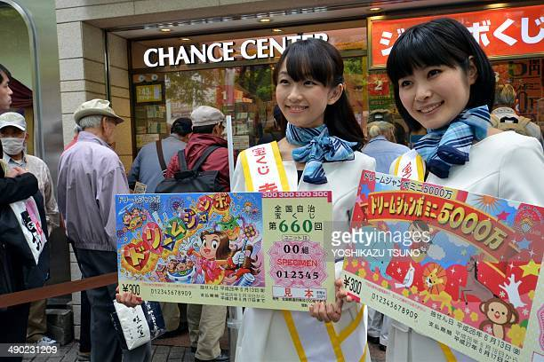 Campaign staff Ayami Tochimura and Shima Arai display sample lottery tickets as people queue to purchase tickets for the 550 million yen 'Dream Jumbo...