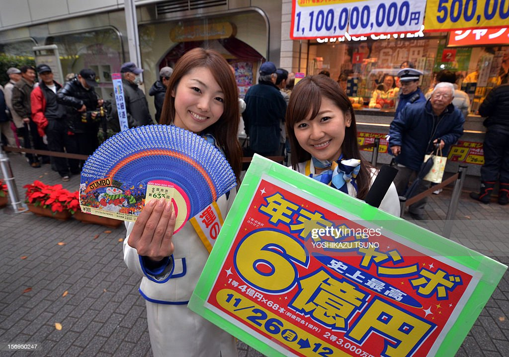Campaign staff Mayuka Nakatani (R) and Kumiko Wakai display sample lottery tickets as people queue to purchase tickets for the 600 million yen (7.3 million USD) year-end Jumbo Lottery in Tokyo on November 26, 2012. Thousands of punters queued up for tickets in the hope of becoming a millionaire. AFP PHOTO / Yoshikazu TSUNO