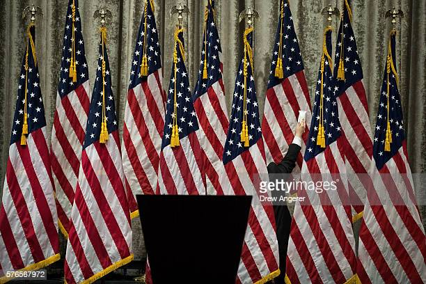 A campaign staffer steams the American flags before Republican presidential candidate Donald Trump and vice presidential running mate Mike Pence...