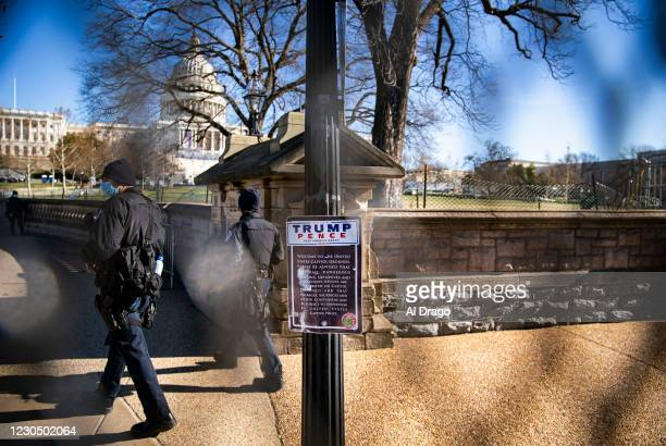 Campaign sticker supporting U.S. President Donald Trump is attached to a sign as U.S. Capitol Police officers walk past, behind security fencing near...