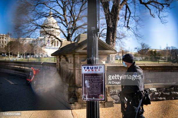 Campaign sticker supporting U.S. President Donald Trump is attached to a sign as a U.S. Capitol Police officer walks past, behind security fencing...