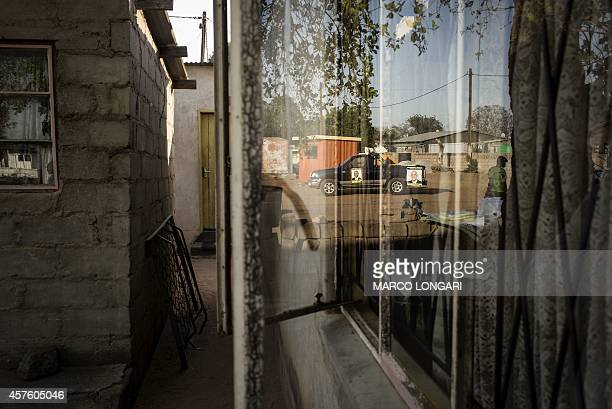 A campaign truck of the oppositione Botswana Congress Party is reflected in the windows of a house in an alley of the Marapula ward of Gaborone on...