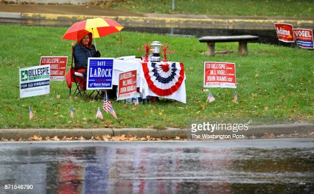 Campaign volunteer for the Republican candidates on the ballot Shelley Oberlander waits in the rain outside the polling place at Hillsboro Old Stone...