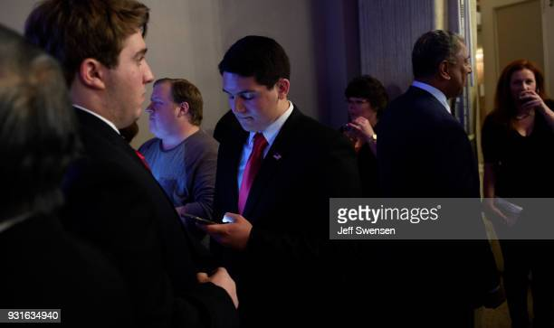 Campaign volunteer Michael Guido center checks early election results on his phone at an Election Night event for GOP PA Congressional Candidate Rick...