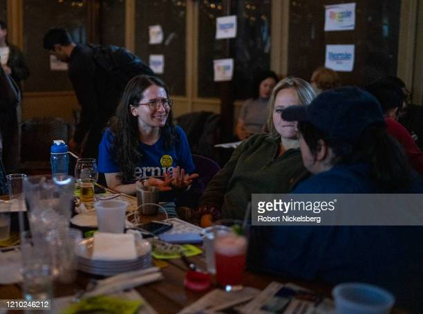 Campaign volunteers for Democratic presidential candidate Sen. Bernie Sanders discuss election headlines at an election watch party on Super Tuesday...