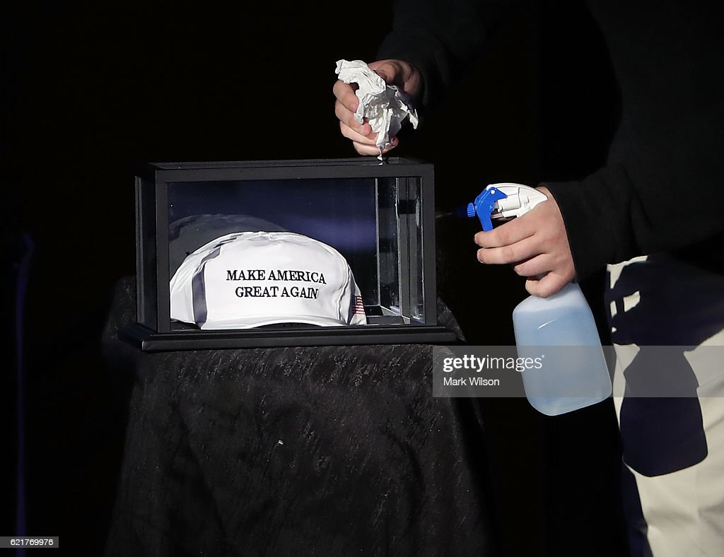 A campaign worker cleans a glass box containing a campaign hat at the Midtown Hilton, where Republican presidential candidate Donald Trumps's election night party will be held, November 8, 2016 in New York City. Today Americans will head to the pools and vote for the next president of the United States.