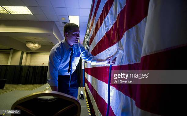 A campaign worker of Republican presidential candidate former Pennsylvania Sen Rick Santorum works on ironing the flag before a rally at the Four...