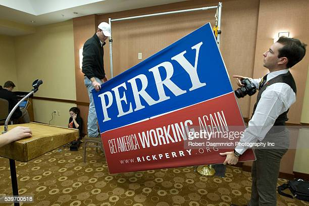 Campaign workers remove a sign as Texas Governor Rick Perry suspends his bid for the Republican presidential nomination with an announcement in...