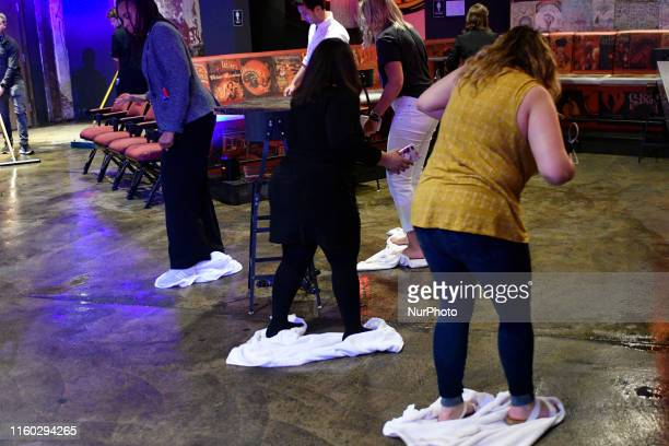 Campaign workers use towels to dry the floor ahead of a rally with Sen Cory Booker at the Fillmore in Philadelphia PA on August 7 2019