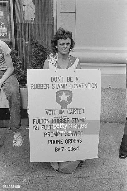 A campaigner for presidential candidate Jimmy Carter with a sign reading 'Don't be a Rubber Stamp Convention Vote Jim Carter' New York City 1976