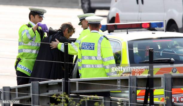 Campaigner Geoffrey Hibbert, who is believed to be linked to Fathers 4 Justice, dressed up as Batman, being escorted away by police officers after he...