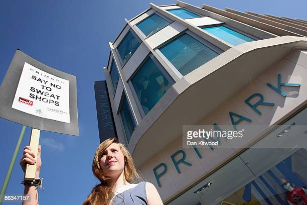 A campaigner holds a banner at a protest over workers pay and working conditions outside Primark on May 2 2009 in London England Activists from the...