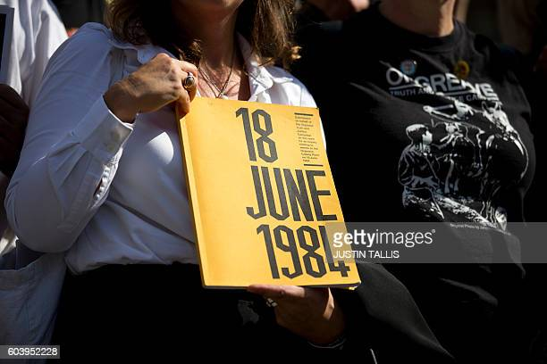 A campaigner holds a book on which the cover reads 18 June 1984 as she stands outside the Houses of Parliament in central London on September 13...