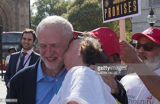 A campaigner kisses British Labour party Leader Jeremy Corbyn on the cheek outside the Houses of Parliament in central London on September 13 during...