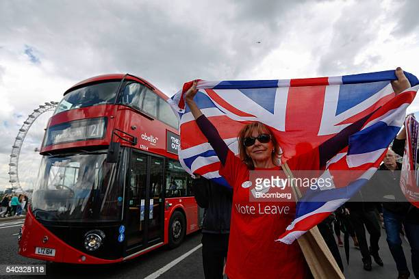 A campaigner wearing a Vote Leave tshirt and holding a British Union Flag also known as a Union Jack stands on a Westminster Bridge near the Houses...