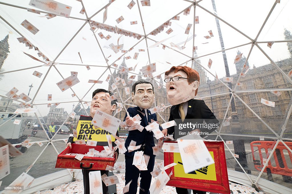 Campaigners dressed as the three chancellors, George Osborne, Ed Balls and Danny Alexander, wearing Oxfams famous big heads take part in a crystal dome cash grab stunt, on March 17, 2015 in London, England. The Tax Dodging Bill campaign is calling on all parties to pledge a series of measures to tackle corportate tax dodging and bring in billions of extra revenue to tackle poverty in the UK.