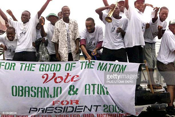 Campaigners for President Olusegun Obasanjo's reelection dance in a moving open truck on a Lagos highway 23 July 2002 The committee responsible for...