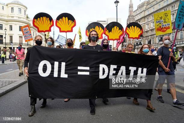 Campaigners from the climate action group Extinction Rebellion hold placards as march from the offices of oil and gas company Shell, towards...