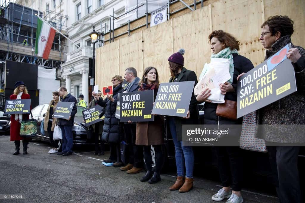 Campaigners hold posters as Richard Ratcliffe, husband of jailed British-Iranian woman Nazanin Zaghari-Ratcliffe, delivers a petition and a letter addressed to the Iranian Deputy Foreign Minister Abbas Araghchi to demand her release, at the Iranian Embassy in London on February 21, 2018. The husband of a British-Iranian citizen jailed in Iran delivered a petition and support letters for his spouse to the country's embassy in London February 21, 2018, amid a visit by a deputy foreign minister. / AFP PHOTO / Tolga Akmen