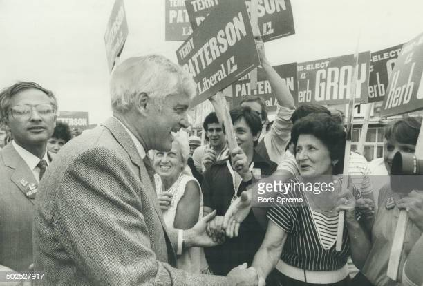 Campaigning Prime Minister John Turner in southern Ontario during much of last week greets supporter against background of campaign posters for...